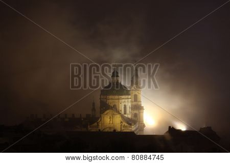 Night fog covering Saint Nicholas Church in Mala Strana in Prague, Czech Republic.