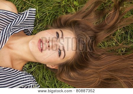 Pretty young long-haired girl lying on the green grass, close-up.