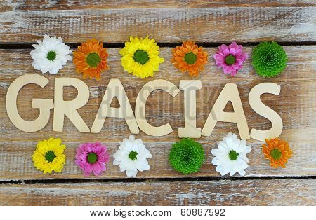 Gracias written with wooden letters on rustic surface and colorful santini flowers