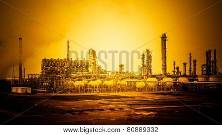 oil refinery with smoke stacks in sunset.