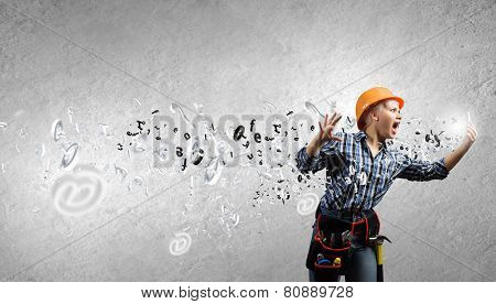 Young emotional woman mechanic screaming in mobile phone