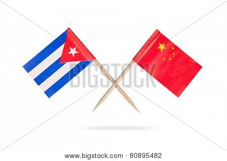 Crossed mini flags Cuba and China with shadow below. Isolated on white background