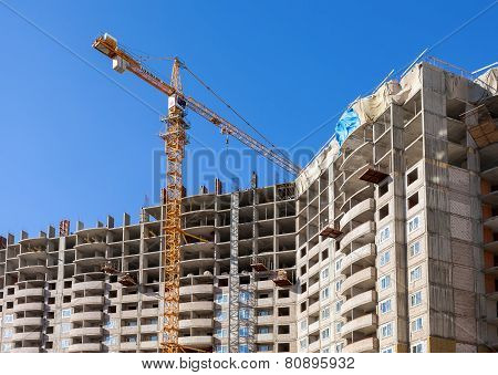 Tall Apartment Buildings Under Construction With Crane Against A Blue Sky Background