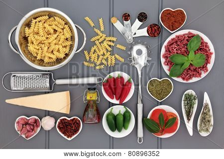 Italian food ingredients and kitchenware over wooden grey background.