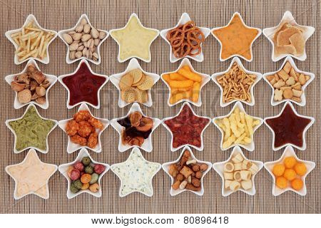 Large crisp and dip snack food selection in porcelain star dishes over bamboo  background.