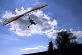 foto of glider  - Motorized hang glider flying to the sun - JPG
