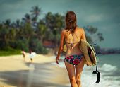 pic of board-walk  - Young lady walking with surf board on sandy tropical beach - JPG