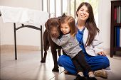 stock photo of working-dogs  - Cute little girl hugging her healthy dog after a visit to the veterinarian - JPG