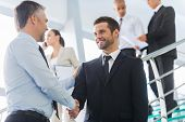stock photo of staircases  - Two confident businessmen shaking hands and smiling while standing at the staircase together with people in the background - JPG