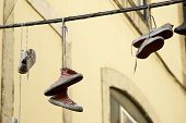 stock photo of prank  - Old sneakers hanging from a cable - JPG