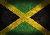 stock photo of jamaican flag  - Old rusty metal sign with a flag  - JPG