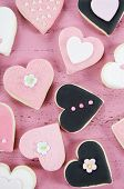 stock photo of shabby chic  - Pink black and white homemade heart shape cookies on vintage shabby chic pink wood background for Valentines Day wedding Mothers Day or female birthday overhead vertical - JPG