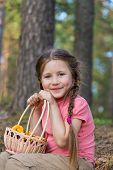 foto of pick up  - Little girl pick up mushrooms in the forest - JPG