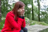 picture of overcoats  - Young woman feeling depressed sitting on a stone table and bench on a forest wearing a red overcoat during winter  - JPG