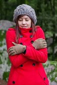 foto of overcoats  - Young woman shivering with cold and embracing herself on a forest wearing a red overcoat - JPG
