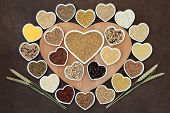 foto of ear  - Grain food selection on a heart shaped wooden board and in porcelain bowls with wheat ears over lokta paper background - JPG