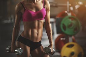 foto of human muscle  - Brutal athletic woman pumping up muscles with dumbbells - JPG