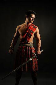foto of sword  - a handsome highlander is holding a sword - JPG
