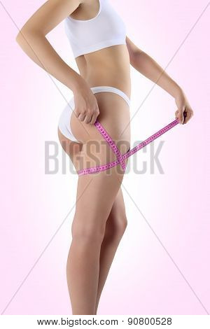 Bum And Legs Of Slim Woman Over Pink Background With Meter