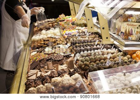 BARCELONA, SPAIN - MAY 4, 2015: Famous La Boqueria market - one of the oldest markets (Established in 1217) in Europe that still exist. Close up on a huge selection of sweets.