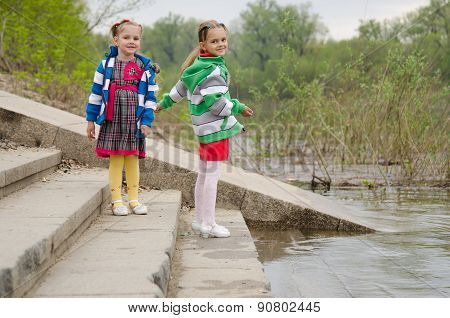 Two Girls Standing On The Steps Near Water