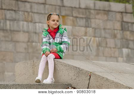 Girl Looks Into Distance While Sitting A Granite Embankment On Ramp