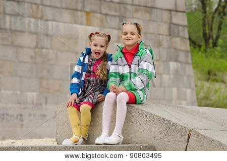 Two Girls Sit On A Granite Staircase