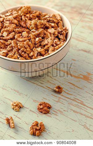 Walnut Kernels In Bowl On Rustic Wooden Background
