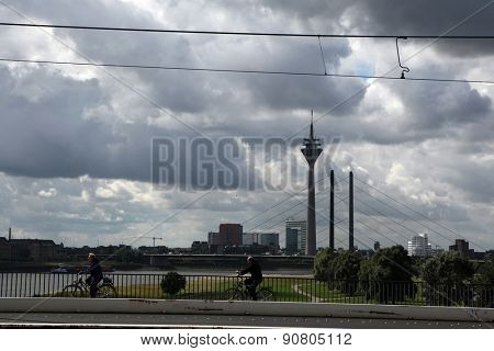 DUSSELDORF, GERMANY - AUGUST 6, 2012: Bikers go in front of the Rheinturm or the Rhine Tower in the Medienhafen District in Dusseldorf, North Rhine-Westphalia, Germany.