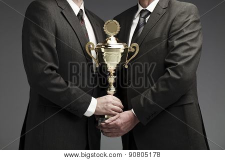 two businessman sharing a trophy
