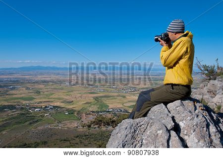 Hiker photographer taking picture of the valley with mountains from view point