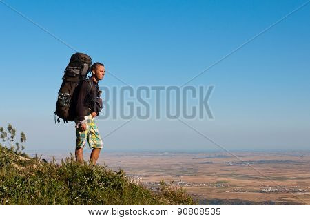 Tourist stands on hill and looks downwards