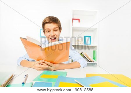 Handsome teen boy read a book sitting at home