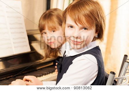 Close-up view of two small girls playing piano