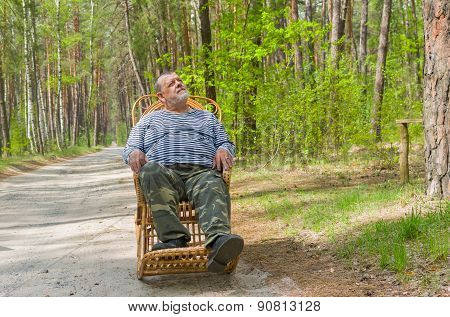Senior man is having rest in forest sitting on a rocking-chair