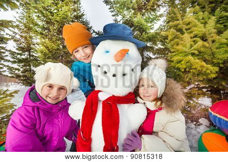 Close-up view of children sitting close to snowman