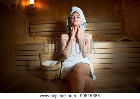 Pretty young  woman sitting relaxed in a wooden sauna.Young woman in white towel sitting in sauna