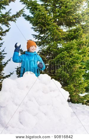 Boy in blue winter jacket throwing snowballs