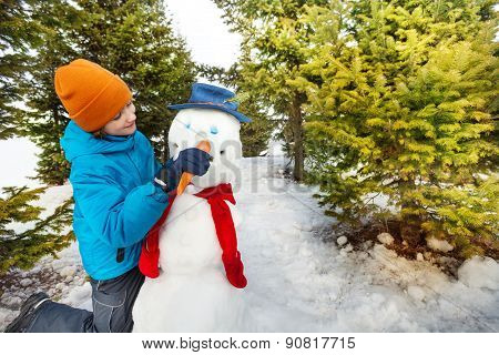 Boy holds carrot to put as nose of snowman