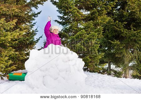 Small girl with snowball stands behind snow wall