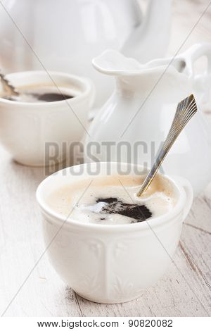 Cup of coffee cubs and milk jug