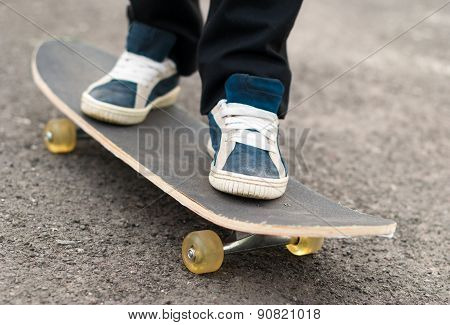 Skateboarder Rides On A Skateboard Feet In Sneakers.
