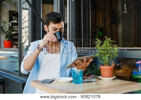 Young Man Drinking Coffee In Sidewalk Cafe And Using Digita Tablet