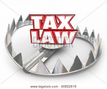 Tax Law words in red 3d letters on a bear trap illustrating legal trouble if you don't follow rules, regulations, guidelines or compliance standards in filing and paying taxes