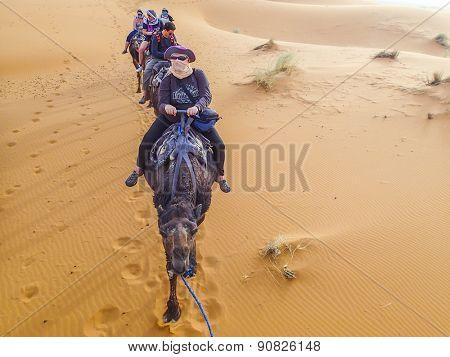 MERZOUGA, MOROCCO, APRIL 13, 2015: Tourists visit Dunes Erg Chebbi near Merzouga during a camel excursion