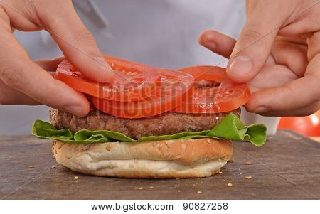 Cook adding tomato on hamburger.Preparing and making hamburger.
