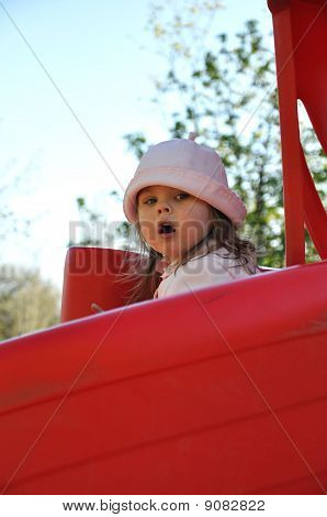 Cute preschool girl riding on slide