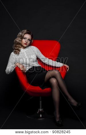 beautiful girl with curly hair in white shirt and skirt on a red chair black background