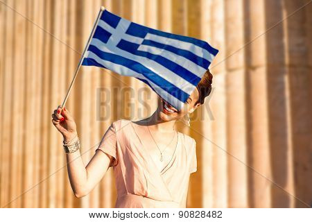 Woman with Greek flag on ancient ruins background