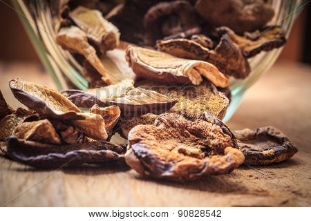 Dry Mushrooms In Jar On Wooden Table.